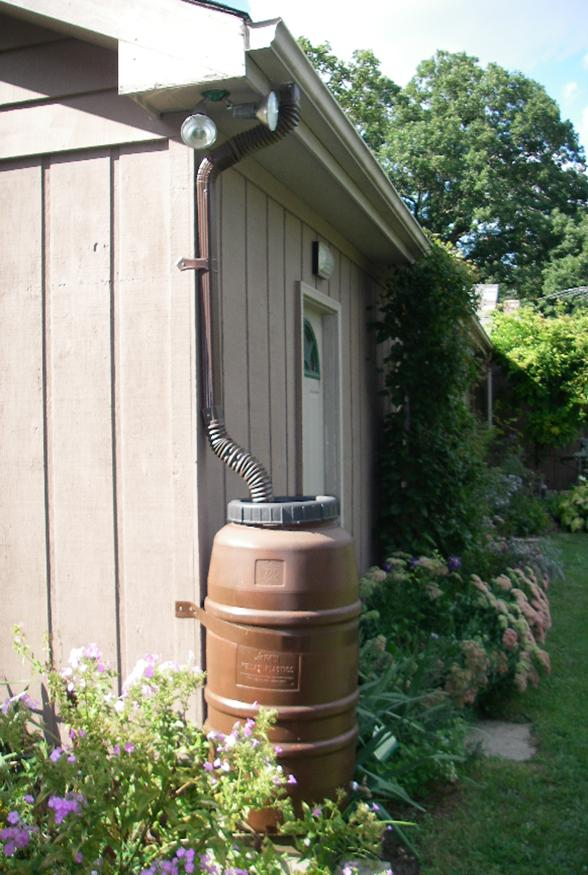 Brown Rain Barrel in Garden Area Attached to Roof Drainage